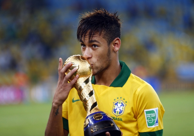 Brazil's Neymar kisses the trophy after winning their Confederations Cup final soccer match against Spain at the Estadio Maracana in Rio de Janeiro June 30, 2013.  REUTERS/Kai Pfaffenbach (BRAZIL  - Tags: SPORT SOCCER)   - RTX117Z7